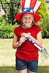 Portrait de fille portant chapeau de Stars and Stripes et tenant Noisemaker Horn