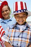 Portrait de garçon coiffé de Stars and Stripes tenant le drapeau