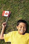 Portrait de garçon couché sur l'herbe, tenant le drapeau canadien
