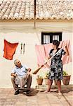 Woman Teasing Husband with Broom