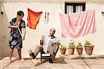 Woman Sweeping Under Husband's Feet