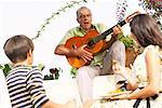 Jouer de la guitare à l'extérieur avec des gens à l'écoute de l'homme