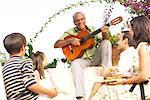 Coin famille écoute à l'extérieur à l'homme qui joue de la guitare