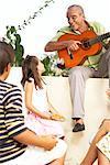 Jouer de la guitare à l'extérieur avec des enfants à l'écoute de l'homme