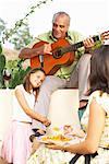 Homme jouant guitare Outdoors et enfant agrippant à sa jambe