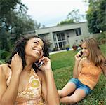 zwei Teenager Freundinnen (16-18) sitzen auf dem Rasen in einen Garten im Gespräch auf dem Handy