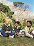 Garçons et filles (7-9) assis sur l'herbe dans les ordinateurs portables, souriant