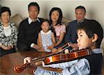 Family Watching Boy Play Violin
