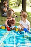 Bébés assis sur une couverture dans le parc