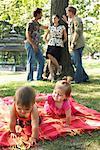 Hommes parler à une femme pendant les bébés jouer dans le parc