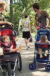 Hommes ayant des bébés en poussette regardant femme Walking Away