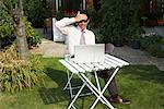 Homme d'affaires avec ordinateur portable en Front Yard