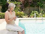 Femme à côté de la piscine à la recherche de la PDA