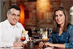 Porträt eines Mitte Erwachsenen Paares sitzen in einem Restaurant mit zwei Gläser Pina colada