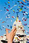 Gros plan de la main d'une personne jetant des confettis à une parade gay