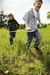 Boys Running Through Field