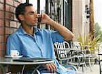 Man sitzend am Café-Tisch und Talking auf Handy