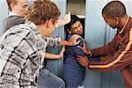 Group of Teens Stuffing Boy in Locker
