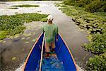Man Steering Boat through River, Antainambalana River, Maroantsetra, Madagascar