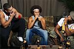 Hommes fumant des cigares sur canapé