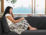 Frau sitzt zu Hause auf Sofa