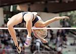 Female high jumper clearing bar