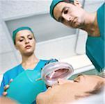 Doctors placing oxygen mask over patient's face