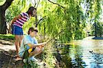 Girl (8-10) watching boy (10-12) fishing in lake, boy crouching