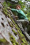 Boy (10-12) climbing rock face