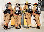 Firefighters Walking towards Smoke-filled Building