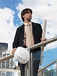 Homme d'affaires détenant des plans détaillés et casque