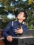 Man on Park Bench Using Laptop Computer