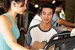 Frau im Fitnessstudio mit Personal Trainer