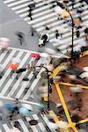 Fußgänger mit Sonnenschirmen an Kreuzung Shibuya, Tokio