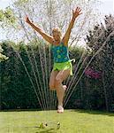 Mature Woman Jumping Through Sprinkler