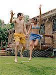 Couple Jumping Through Spinkler
