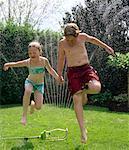 Siblings Running Through Sprinkler
