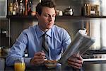 Mann lesen Zeitung beim Frühstück