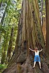 Woman Hugging Redwood Tree, Humboldt Redwoods State Park, California, USA