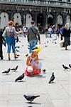 Girl crouching near pigeons, Venice, Veneto, Italy