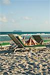 Profil de côté d'une femme allongée sur une chaise longue sur la plage