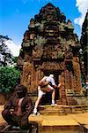 Rear view of a man peeking into a temple, Banteay Srei, Angkor, Siem Reap, Cambodia