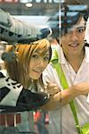 Couple d'adolescents à la recherche dans la fenêtre de magasin de chaussure