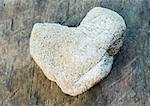 Heart shaped stone on wood background
