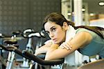Femme sur le vélo d'exercice, penché en avant, se reposer sur les barres de poignée