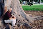 Man Sitting at Base of Tree