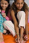 Two preteen girls painting toenails