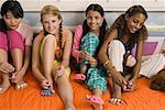 Four preteen girls painting toenails