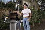 Portrait of a mature man preparing grill steak
