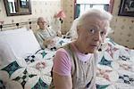 Worried senior woman sitting on bed with bedridden senior man
